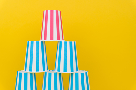 stack of colorful party paper cups on yellow background 免版税图像