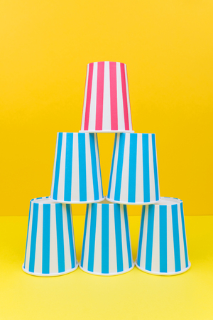 stack of colorful party paper cups on yellow background Stockfoto