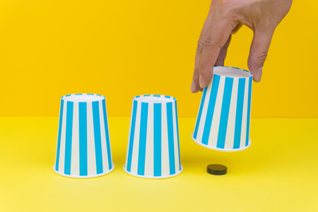 Hand lifting up a blue party paper cup and found a black wooden round object, yellow background