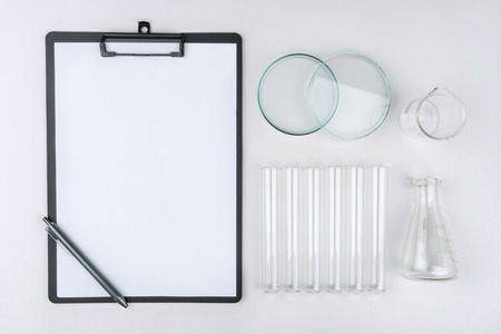 top view of laboratory equipments. A clipboard with pen, flask, test tubes, Petri dish and beaker on the table