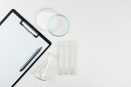 top view of laboratory equipments. A clipboard with pen, flask, test tubes and Petri dish on the table