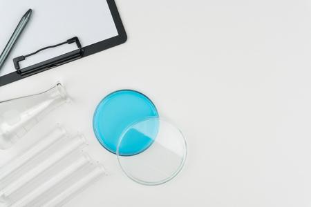 Draufsicht einer Petrischale mit blauer Flüssigkeit, einem Kolben, den Reagenzgläsern und einer Zwischenablage mit Stift auf dem weißen Tisch.