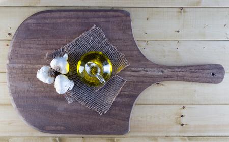 Fresh Garlic Bulbs and Olive Oil on Rustic Board