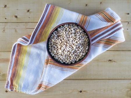 pine nuts: Pinoli in ceramica ciotola sul tovagliolo d'epoca