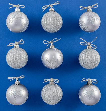 Sparkly Silver Ornaments on Vibrant Blue Background Reklamní fotografie