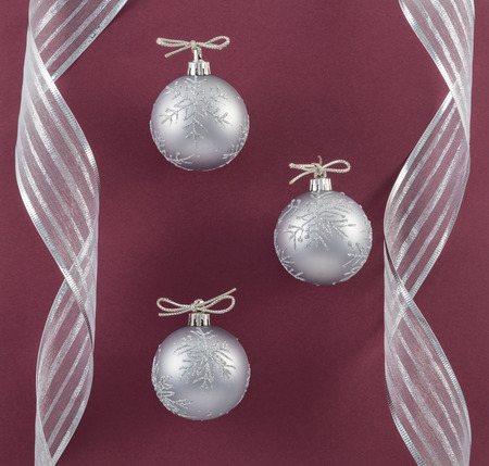 Silver Ornaments and Ribbon on Merlot Background
