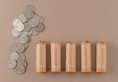 Coin-Wrapped and Loose Quarters on Tan Background Reklamní fotografie