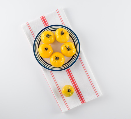 Yellow Heirloom Tomatoes on Stoneware Plate and French Towel