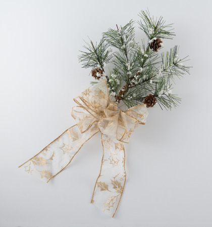 Pine Bough Decoration with Sparkly Gold Bow on White Background