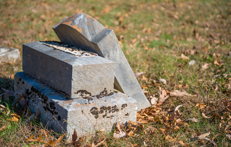 gravesite: Neglected Tombstone in Autumn Leaves
