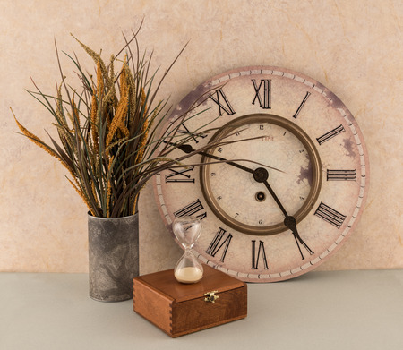 Clock and Hourglass with Floral Arrangement and Old Wooden Box