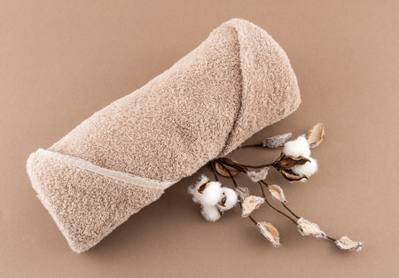 Spa Luxury Towel and Cotton Branch on Tan Background