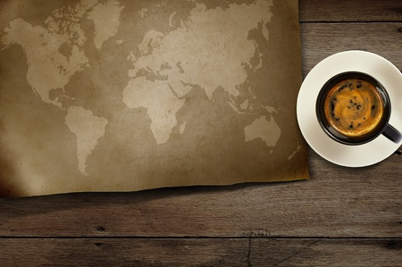 vintage world map and coffee on wooden photo