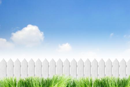 cerca blanca: Valla de color blanco con hierba en el cielo azul claro Foto de archivo