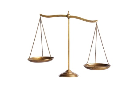 scale model: unbalance of golden brass scales of justice on white