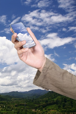green computing: Businessman holding his mobile phone on cloud
