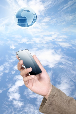 world connectivity: mobile phone with human hand on sky Stock Photo