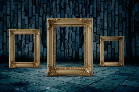 Three blank, white frames on a brick wall.
