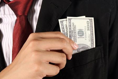 bolsa dinero: Hombre de negocios poner billetes de dólar en el bolsillo