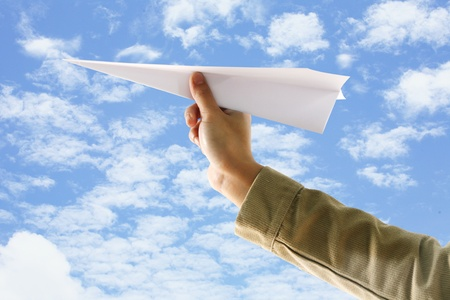 hand with paper plane on  blue sky  photo