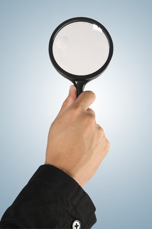 Magnifying glass in hand  on blue background  (path in side)  photo