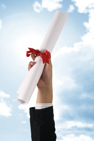 Diploma with a red ribbon in hand on sky photo
