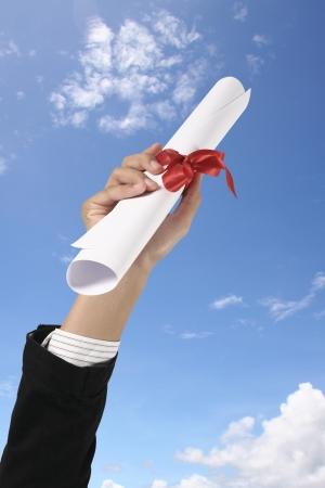 egresado: Diploma con una cinta roja en la mano en el cielo