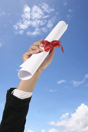 college graduate: Diploma with a red ribbon in hand on sky Stock Photo