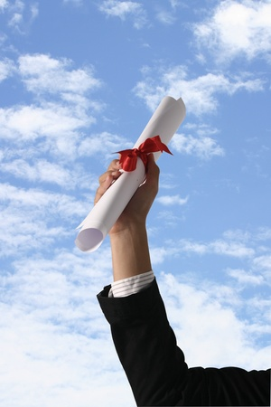 shimmery: Diploma with a red ribbon in hand on sky Stock Photo