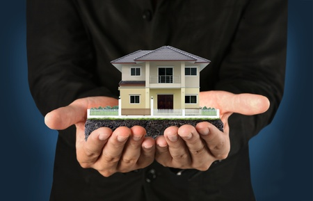 yellow house: Yellow house in hands  Stock Photo