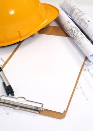 yellow hard hat and blueprints background Stock Photo - 10849809