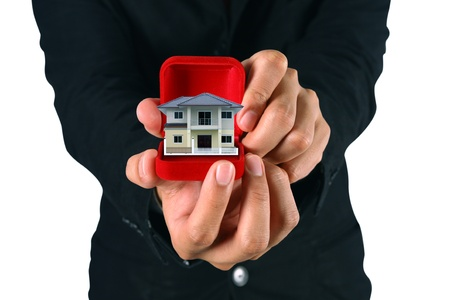 Hand of the businessman with house on red velvet boxes. photo