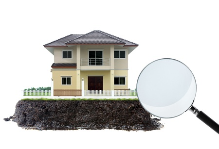 house and magnifying glass, on white  photo