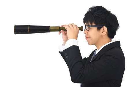 asia young business man looks through a telescope photo