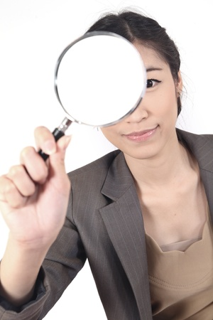 appalled: Confident young woman looking through a magnifying glass isolated (blank space for text)
