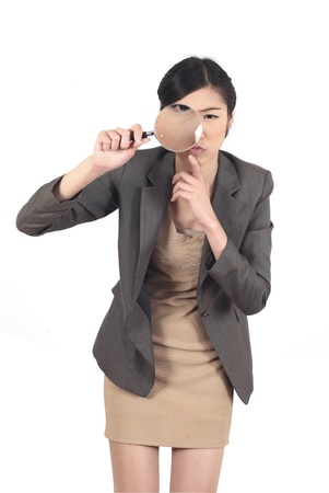 Confident young woman looking through a magnifying glass isolated  photo