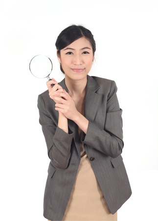 Confident young woman looking through a magnifying glass isolated