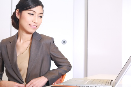 Young business woman on a laptop at her office   photo