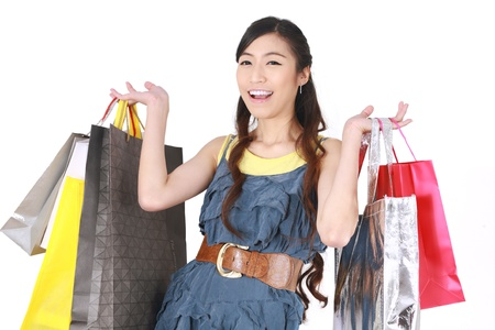Shopping woman happy smiling holding shopping bags on white background.   photo