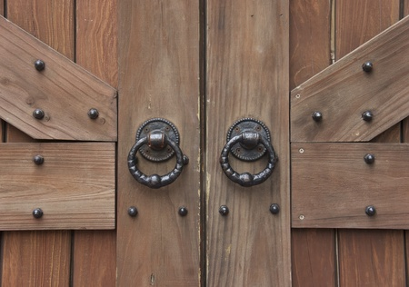 ancient wooden gate with two door knocker rings close-up             photo