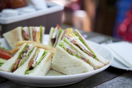 sandwich de pollo: Club de sándwich con café sobre fondo de madera Foto de archivo