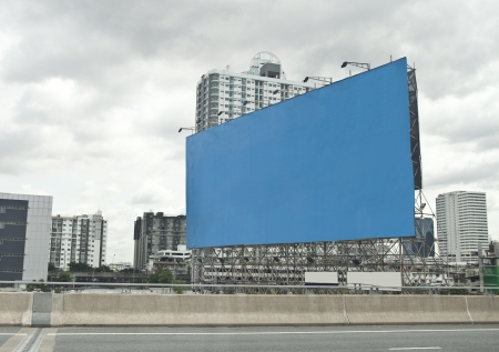 outdoor advertising: blue empty billboard on city.