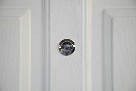 eyewitness: door lens peephole on white wooden texture  Stock Photo