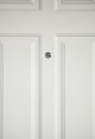 eyewitness: white wooden door and lens peephole.