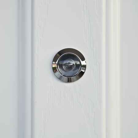 peep: close up, door lens peephole on white wooden texture  Stock Photo