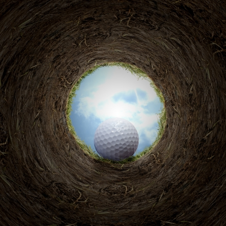 near: Golf ball falling in cup. Stock Photo
