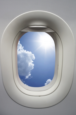 airplane window: View above clouds from window with airplane  Stock Photo