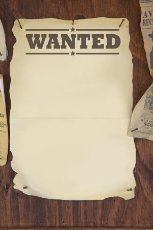 wanted notice paper on old wooden background  photo