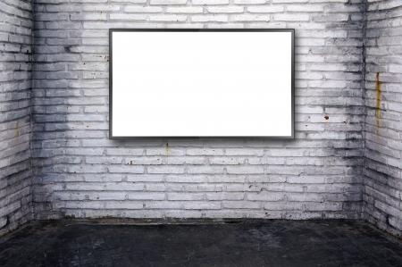 Blank modern flat screen at grunge brick wall background.