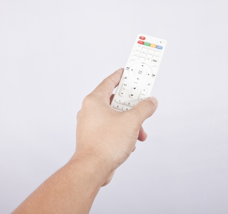 Hand with TV remote control on white  photo